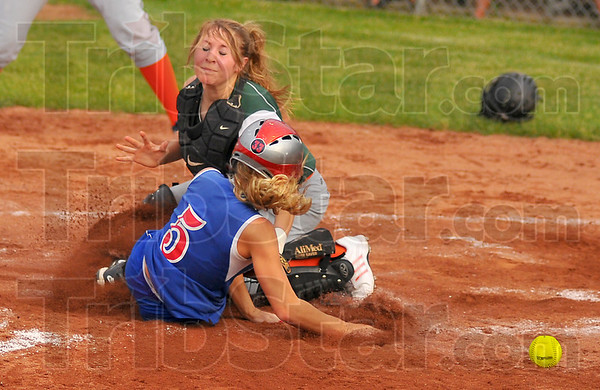 Safe: Linton baserunnerJannae Jackson slides safe into home as the throw gets away from Wheeler catcher Caitlin Herzog.
