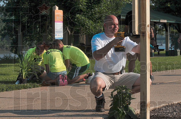 Tribune-Star/Joseph C. Garza<br /> Day of action: Troy Fears, executive director of the United Way of the Wabash Valley, fastens a sign onto a post as part of the United Way's Day of Action Friday at Fairbanks Park.