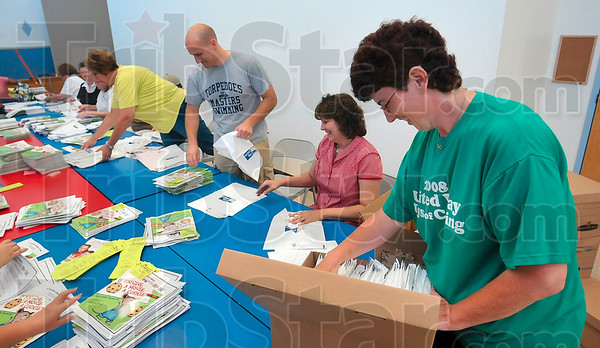 Tribune-Star/Joseph C. Garza<br /> Assembly line proficiency: Eli Lilly employee Darla Vanatti packages Success by Six program packets as part of a United Way Day of Action group effort Friday at Head Start.