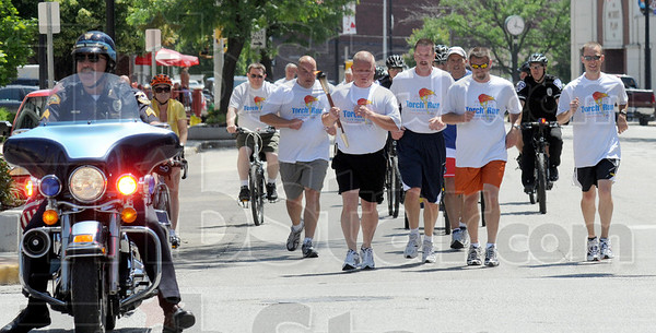 Torch run: A group of police officers run along Wabash Avenue Friday afternoon carrying the Special Olympics Torch.