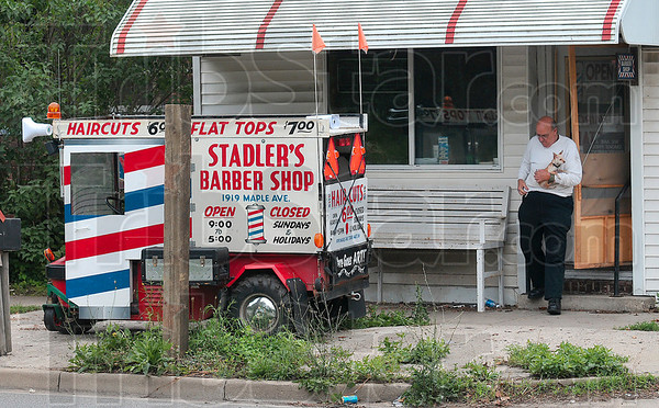 Tribune-Star/Joseph C. Garza<br /> Time to go, Peanut: Stadler's Barber Shop owner, Art Stadler, closes up shop for the day as he carries his pet Chihuahua, Peanut, with him Monday at 1919 Maple Avenue.