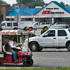 "Tribune-Star/Joseph C. Garza<br /> ""Putt, putt, putt, putt, here goes Art!"": After picking up his grandson, Jonathan Berry, 15, Art Stadler drives along Wabash Avenue in his Stadler's Barber Shop cart Monday on his way home in Clay County."