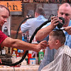 Tribune-Star/Joseph C. Garza<br /> Father and son business: Paul Piper feeds his six-year-old son, Carson Piper, some candy out of a vending machine at Stadler Barber Shop Monday as barber John Stadler trims up the youngster.