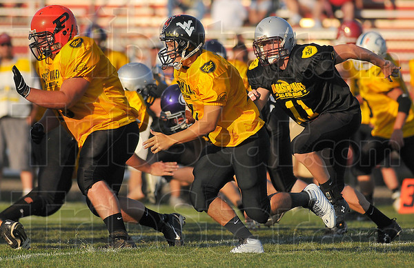 Coming through: Jordan Keyes, left, of Paris leads the blocking for North quarterback Landon Keith of West Vigo. Catchng up from behind is South defender Theo Lane of Robinson.