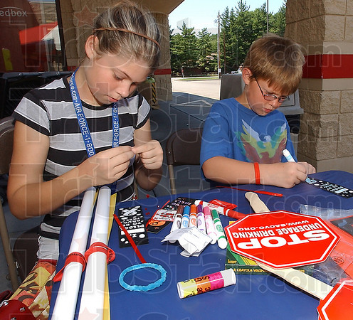 Crafty: Emily Isbell constructs an ankle bracelet while her brother Dakota colors a book mark at the drinking awareness event at Baesler's Market Saturday afternon.