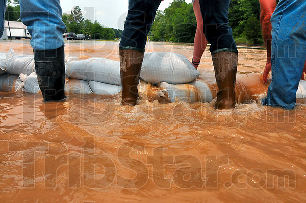 Tribune-Star file photo/Jim Avelis<br /> Hold the line: Volunteers stack sandbags across US 40 west of West Terre Haute to try to save the town from the floodwaters of Sugar Creek Saturday, June 7, 2008.