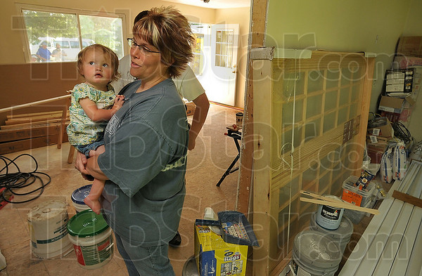 Tribune-Star/Joseph C. Garza<br /> Missing home: Prairie Park subdivision resident Christi Reinig holds her niece, Lakyn Hadley, as Reinig talks Friday about the renovations being done to her home that was damaged by the June 2008 floods.
