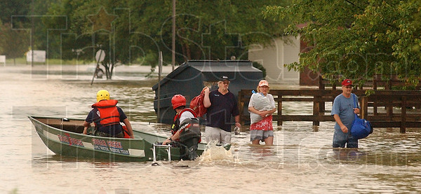 Tribune-Star file photo/Jim Avelis<br /> They carried what they could: Winthrop Court residents Mark Marquis and Michelle Moulton walk past a water rescue boat from the Sugar Creek Volunteer Fire Department that was heading into The Crossings to help stranded residents.