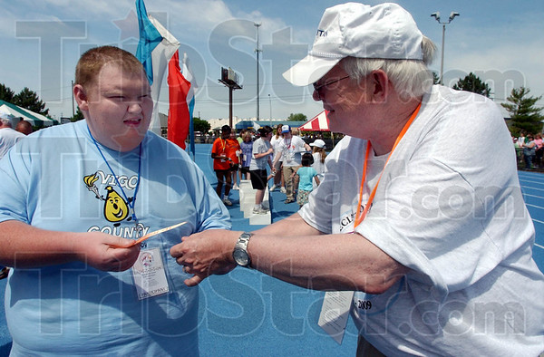 Congratulations: Eric Johnson recieves his ribbon from Special Olympics volunteer Duane Chatlin of Vincennes. Johnson had just competed in the 100 meter dash.