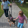 Fit for petting: Six-year-old Kendra Miller of Linton pets Tammy South's dobie mix, Raja, as they walk in 1-K-9 Saturday at Memorial Stadium.