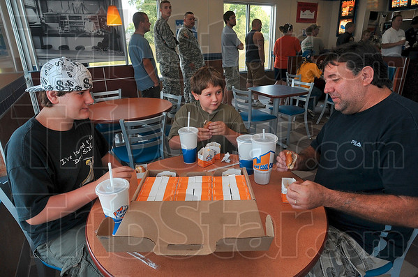 "Tribune-Star/Joseph C. Garza<br /> ""This is a blessing!"": Terry Shattuck of West Terre Haute savors every bite of his white castle hamburger as he enjoys a ""crave case"" with his sons, Brandon Shattuck, 14, and Skylar Shattuck, 9, at the new restaurant Tuesday."