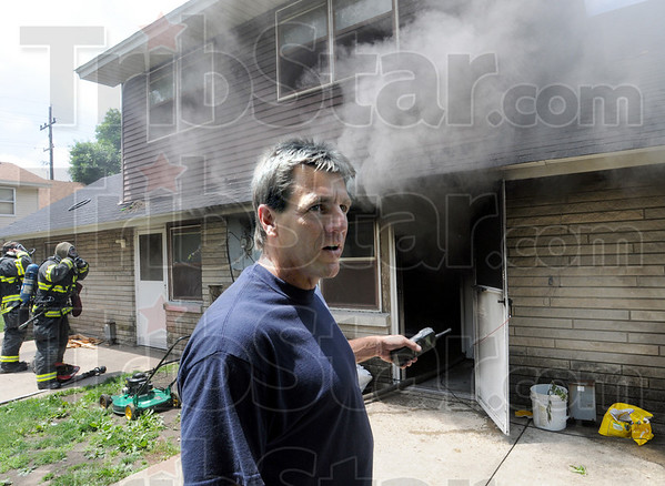 On scene: Terre Haute fire department investigator Jeff Hodges talks with firefighters at the scene of a fire in the Margaret Avenue housing project Wednesday afternoon. The original call to 911 indicated that a can of gasoline ignited near a water heater in the apartment.