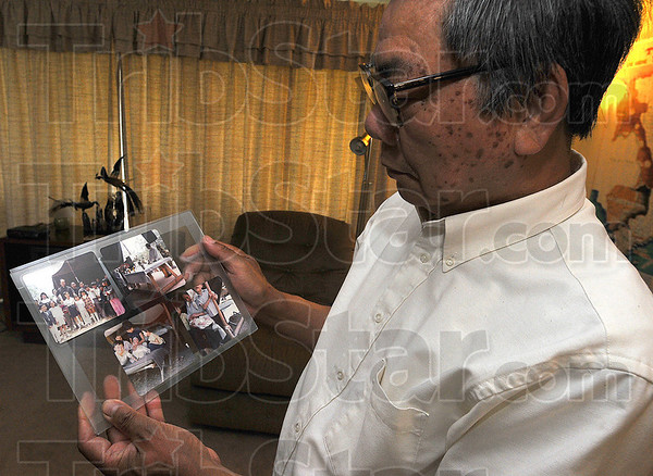 All about family: Joseph Vu holds a collage of family photographs. He and his wife Terese celebrated their 50th wedding anniversary last weekend.