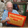 Back on the job: Cecil Tilford seals up an envelope of registered mail at the end of hours Monday.