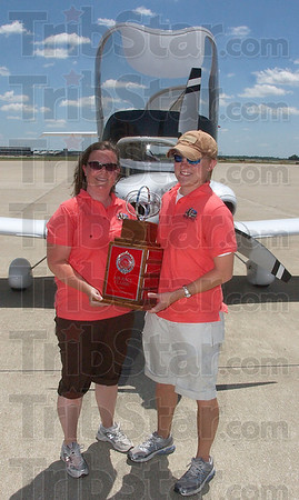 Seasoned fliers: Virginia Dunbar and Jessica Campbell hold their Collegiate Challenge trophy in front of the Diamond DA40 aircraft they flew in the 80th annual Air Race Classic last week. The craft was loaned to them by Dixie Chopper Air.