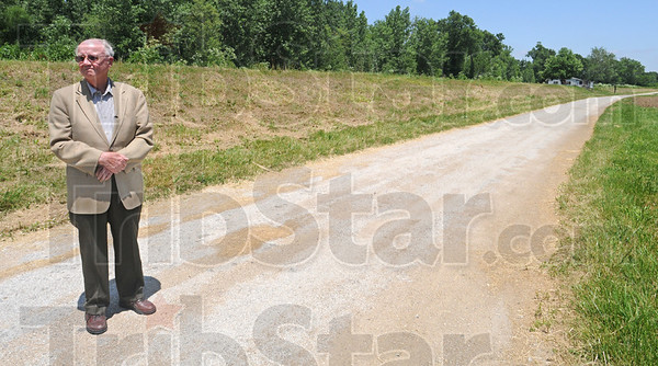 Not happy: John T. Newlin stands along the section of the Robertson Road he says the County will no longer maintain Tuesday afternoon.