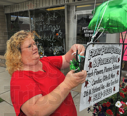 "Home town pride: Trish Schoffstall hangs balloons from the sign in front of her West Terre Haute Business ""Front Porch Friends & Flowers Too!"" Tuesday afternoon. The display was in support of the West Vigo High School baseball team, making its first appearance ever in the state finals."