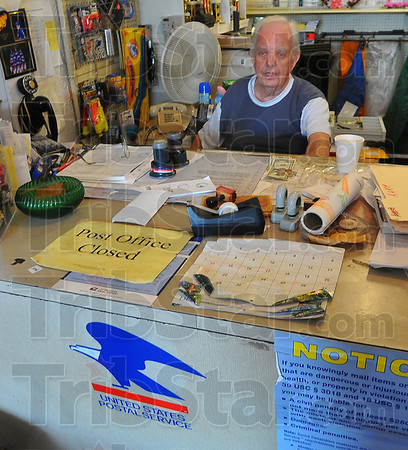 Slow day: Cecil Tilford sits behind the counter of his variety store in Twelve Points. Since the U.S. Postal Service has suspended operations out of his store, Tilford has seen business fall off well over half.