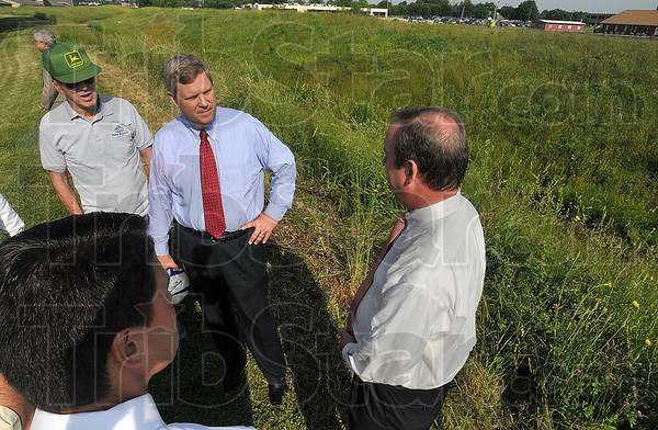 Tribune-Star/Joseph C. Garza<br /> Protecting against future flooding: Agriculture Secretary Tom Vilsack, center, talks with Honey Creek-Vigo Conservancy District Board attorney, Craig McKee, right, and Congressman Brad Ellsworth, lower left, after a press conference near Thompson Ditch off of Seventh Street Tuesday.