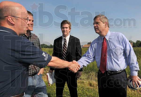 Tribune-Star/Joseph C. Garza<br /> Meeting the ones directly affected by the '08 flood: Parker Manning, a member of the Honey Creek-Vigo Conservancy District Board, shakes hands with Agriculture Secretary Tom Vilsack after Vilsack looked over Thompson Ditch during his visit Tuesday near the ditch off of Seventh Street.