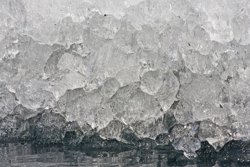 Melting glacier ice forms peculiar patterns as it disappears into the water.