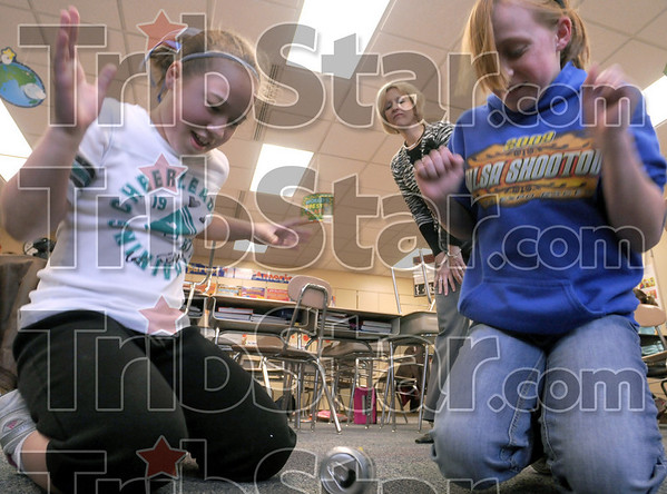 Experiment:  Kylie Cardinal and Maddie Funk experiment with a can and a rubber band as their teacher Teresa Stuckey monitors Thursday afternoon at Consolidated School.
