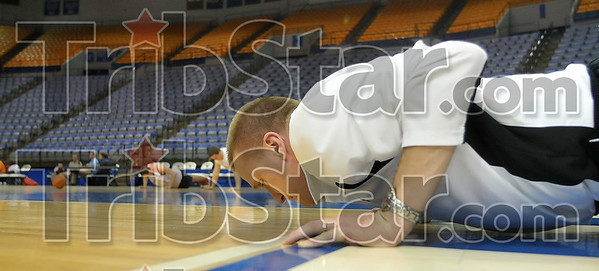 Tribune-Star/Joseph C. Garza<br /> Setting the example: Marshall, Ill., High School boys basketball coach Tom Brannan does push-ups with his white-jerseyed practice squad during team practice Monday at Hulman Center.