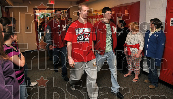 Tribune-Star/Joseph C. Garza<br /> March of the Lions: Members of the Marshall, Ill., High School boys basketball team, including Logan Eitel and Taylor Duncan, walk through the hallway of the school to the applause of fellow students and staff members before boarding a bus bound for Peoria.
