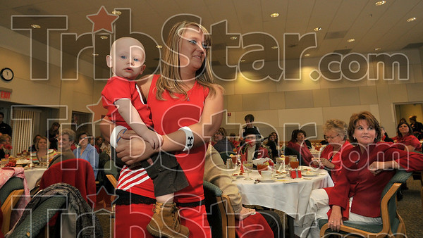 Tribune-Star/Joseph C. Garza<br /> Seeing red (for a good cause): Sarah Wright carries her 14-month-old son, Tyeler Wright, as she models an athletic outfit during the first annual Essence of Red Ñ Heart, Mind, & Moxie event to promote womenÕs heart health Thursday at Rose-Hulman.