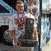 Trophy time: A Marshall player carries the trophy as he exits the team bus after returning from Peoria Sunday afternoon.