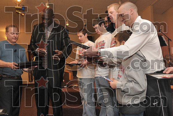 Tribune-Star/Joseph C. Garza<br /> A token of appreciation: Marshall boys basketball coach Tom Brannan, right, looks over a plaque after he received it from New Life New Beginnings Church Pastor Tim Foster, left, and former NBA player Ray Tolbert, center, Sunday in Marshall.