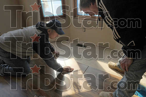 Hands-on: Don Eiler and Bob Fuller lay some laminate flooring in a home they in the process of building Friday afternoon.