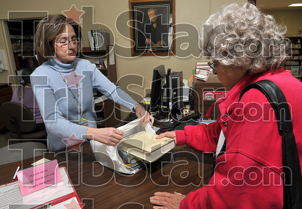 Tribune-Star/Joseph C. Garza<br /> Carnegie's legacy: Library Director Cindy Hein helps bag books with patron Wanda Scott near a picture of Andrew Carnegie Tuesday at the Rockville Public Library.
