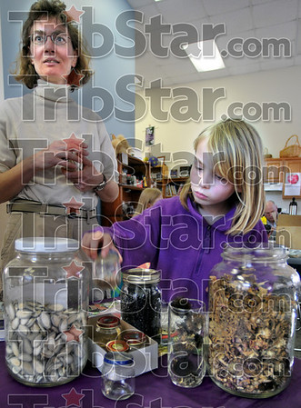 Seed savers: Seven-year-old anne Hoffman gets introduced to seed saving by her mother Sharon Saturday morning at the White Violet Center.
