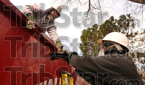 Tribune-Star/Joseph C. Garza<br /> Team work: Delta College student Shawna Fleming, 21, of Glennie, Mich., takes old house shingles from Miami of Ohio University student Ashley Stucky, 19, of St. Louis as they help demolish a home Wednesday on Taft Street as part of their alternative spring break.
