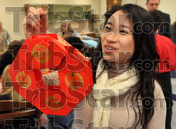 Tribune-Star/Joseph C. Garza<br /> New Year coin: Hong Kong teacher Vivian Wong shows an example of a Chinese New Year decoration Wednesday at South Vermillion High School. The decoration is shaped like a Chinese coin.