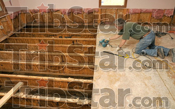 Tribune-Star/Joseph C. Garza<br /> Work in progress: Contractor John Conner cuts out panels of the floor in the Montessori School on south 11th Street Wednesday. The school was heavily damaged by the floods last June.