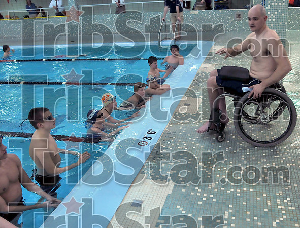 Free lessons: Paralympian Dave Denniston gives instructions on swimming a better breaststroke to a group of swimmers Wednesday afternon in the Terre Haute South Vigo High School pool.