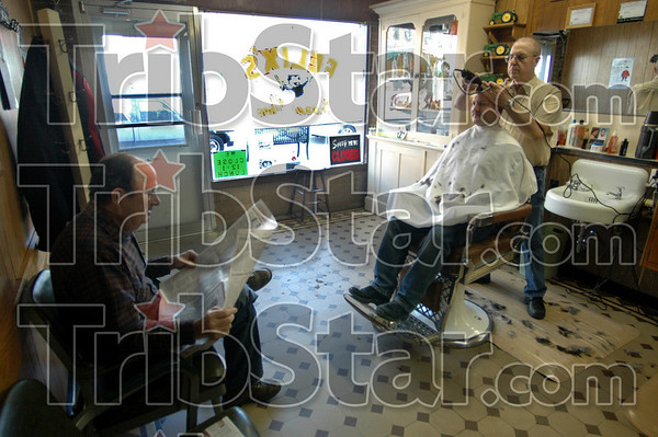 Lion supporters: Ken Mackey (L) reads the sports story about Marshall's victory over Robinson as he waits for his turn in the chair at Felix's barber shop. Barber Felix Farrell gives Matt Beetz a buzz cut.