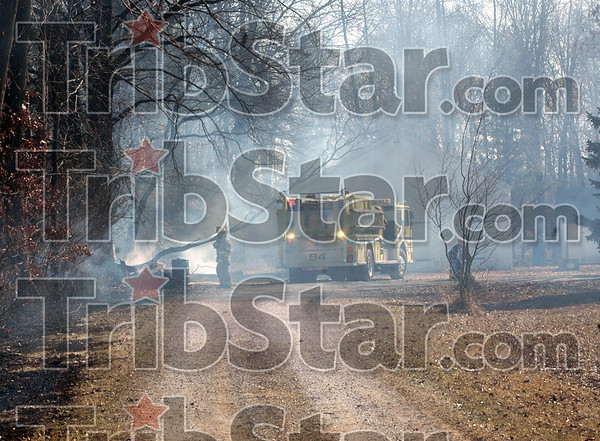 Smoke gets in your eyes: A Honey Creek fire unit sits in a driveway off Margaret Drive as they and other volunteers attempt to extinguish a brush fire that ignited a large storeage building causing it and its contents to be a total loss.