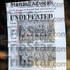 Undefeated: A newspaper clipping taped to the glass of a storefront on the Marshall square touts the three undefeated boy's basketball teams.