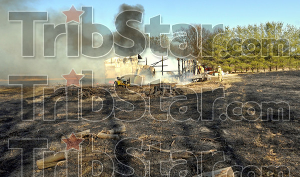 Brush fire: Volunteer firefighters douse hot spots in a storeage building that was totally destroyed by a wildfire Wednesday afternoon in the 8900 block of E. Margaret Drive.