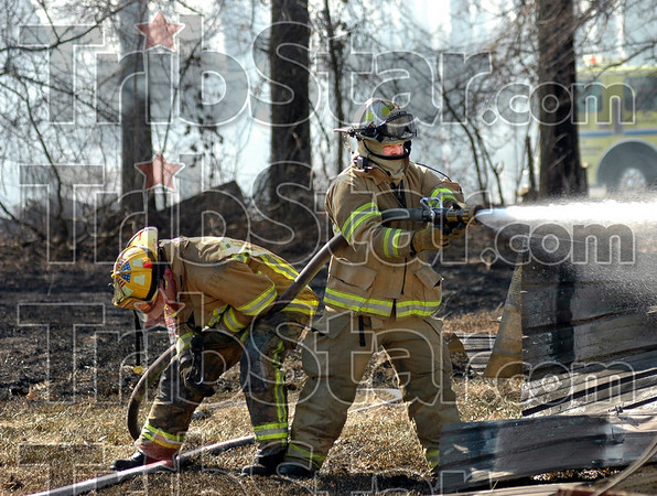 Scorched: A firefighters catches his breath while assisting Honey Creek's Tom High as he pours water onto the remains of a storeage building just off E. Margaret Drive in approximately the 8900 block.