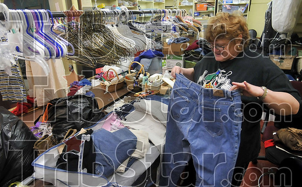 Tribune-Star/Joseph C. Garza<br /> Ready for the rack: Volunteer Pat Ellington folds a pair of jeans as she works in the donation receiving area of The Family Life Center in Bloomfield Monday.