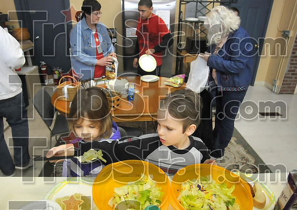 Tribune-Star/Joseph C. Garza<br /> A full plate for everyone: Eight-year-old James Vester helps his sister, Cheyenne, 6, with a portion of salad during their visit to The Family Life Center in Bloomfield Monday. Lunch is often served during the lunch hour for anyone in the center at the time.