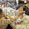 Tribune-Star/Joseph C. Garza<br /> Meeting needs: One-year-old Monique Pettus of Jasonville takes a bite of spaghetti from her mother, Tosha Pettus, as they take a break from browsing the free store at The Family Life Center in Bloomfield Monday.