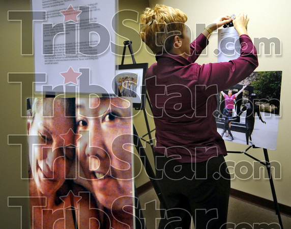 Lilly USA: Sarah Burke prepares an art and photography exhibit for display at the Hux Cancer Center Tuesday afternoon.