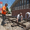Measure twice: Alan Ervin of Indiana Railways waits for David Black and Kiel Majewski to get the correct measurements for the setting of railroad rails in front of the C.A.N.D.L.E.S. Museum on south Third Street. The rails symbolize the trains that brought so many pople to the concentration camps during WWII.