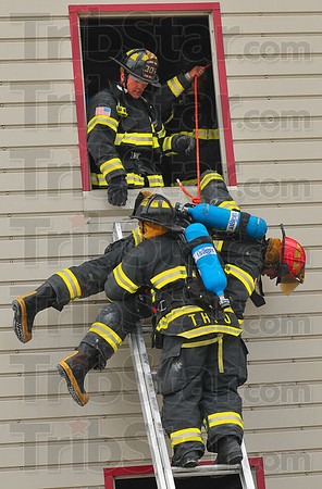 Down to safety: Terre Haute firefighter Kevin Price lowers Cpt. Mitchell Hunt down a ladder while Kevin Kull watches, after lifting Hunt out the window.