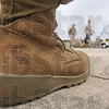 Tribune-Star/Joseph C. Garza<br /> Boots on the ground: Like the boots worn by his fellow marines, Staff Sgt. Leon Crandell of Company K, 3rd Battalion, 24th Marines, wears the U.S. Marine Corps logo on his own pair as he watches them load the plane for deployment Thursday at the Terre Haute International Airport.